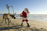 Santa Claus, Tim Connaghan of The Kringle Group, LLC, walks a reindeer from California Reindeer Rentals along the shore in Huntington Beach, Calif. ///ADDITIONAL INFORMATION: christmasdaycover – 12/20/12 – PHOTO ILLUSTRATION BY LEONARD ORTIZ, ORANGE COUNTY REGISTER – Christmas Day 2012 cover photo of Santa Claus on the beach in Huntington Beach with a live reindeer.